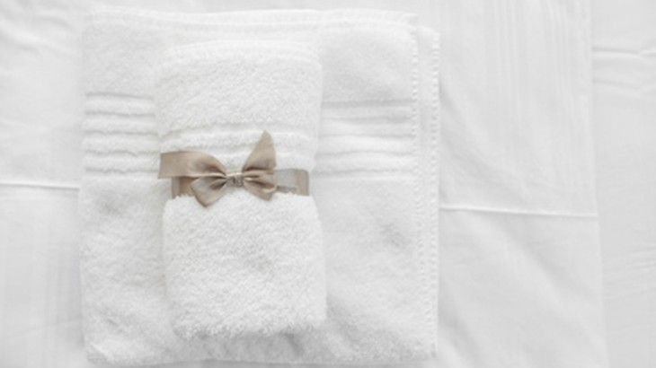White towels with grey ribbon folded on white sheets